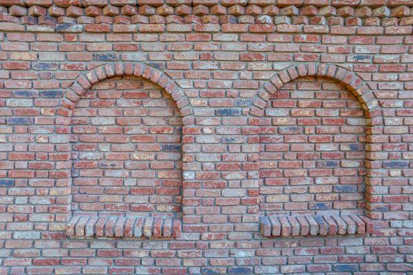 Backsteinmauer mit Blindfenster und Schmuckband